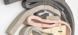 Twisted bars of cement, polyurethane, and foam in pastel colors over a white wall