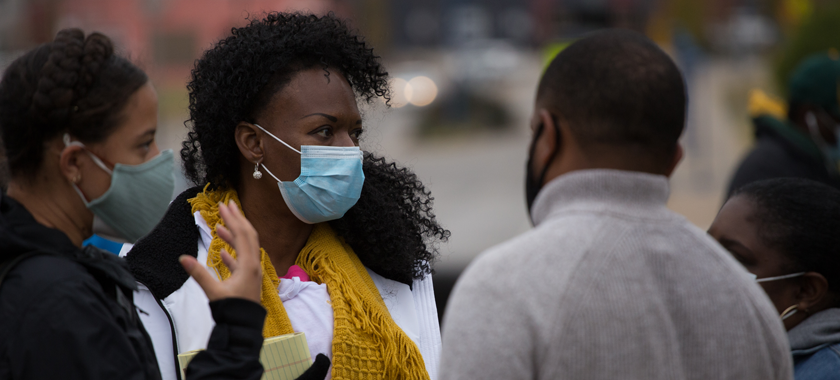 Image: A group of four people confer--all wearing masks--against a blurred background.