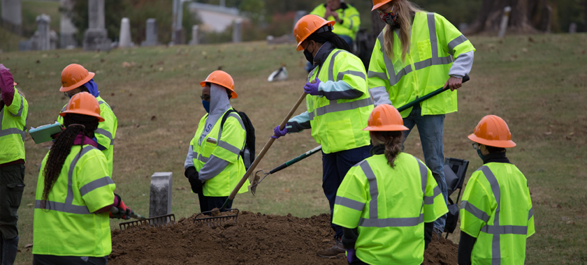 Image: A team of forensic archeologists excavate a suspected mass grave wearing bright green jackets and orange hard hats.