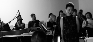 Image: Black and white image of Eunbi Kim standing in front of a piano as the audience around her applauds.