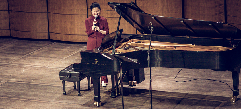 Image: Eunbi Kim stands on stage with a microphone in hand, addressing an unseen crowd at The Kennedy Center in Washington, DC.
