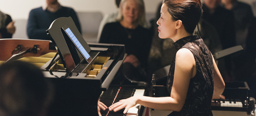 Image: Photograph of Eunbi Kim performing at Korean Cultural Center NY. She is playing two pianos at once while reading music off of an electronic device.