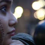 Image: Close-up profile photo of a woman's face. She wears a headscarf and rests her chin on her hands, looking upwards as lights twinkle in the background.