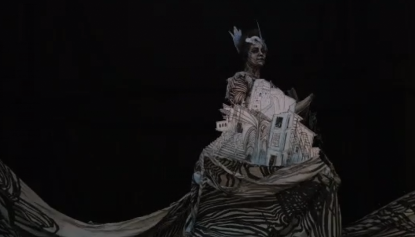 Image: Stop-motion animation still of a woman painted in black and white against a black background. She wears a cut-out of buildings on her dress, which flows into a sweeping, wave-like gesture at the bottom of the screen.