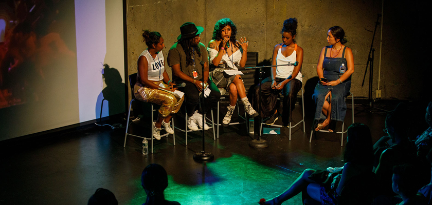 Image: Five individuals sit on raised chairs on a spotlit stage, one with a microphone in hand. A crowd sits in chairs before them.