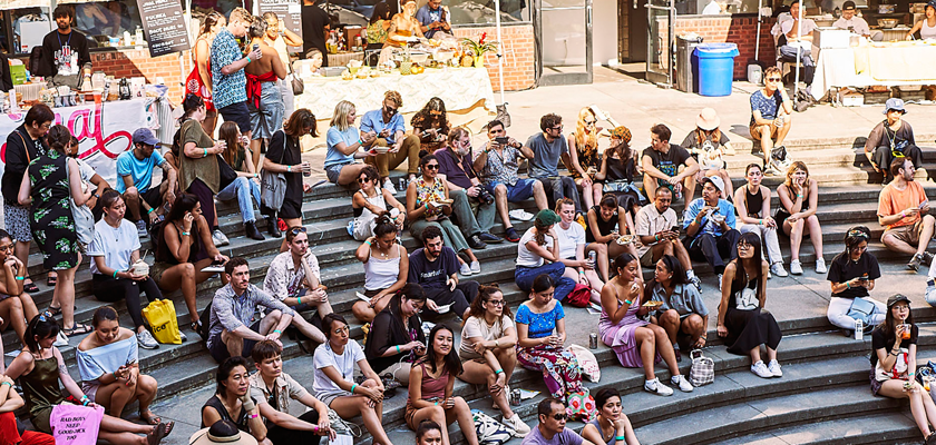 Image: A crowd gathers in the outdoor amphitheater, opposite the music stage at Happy Family Night Market 2019. Behind them are vendors seated behind tables.