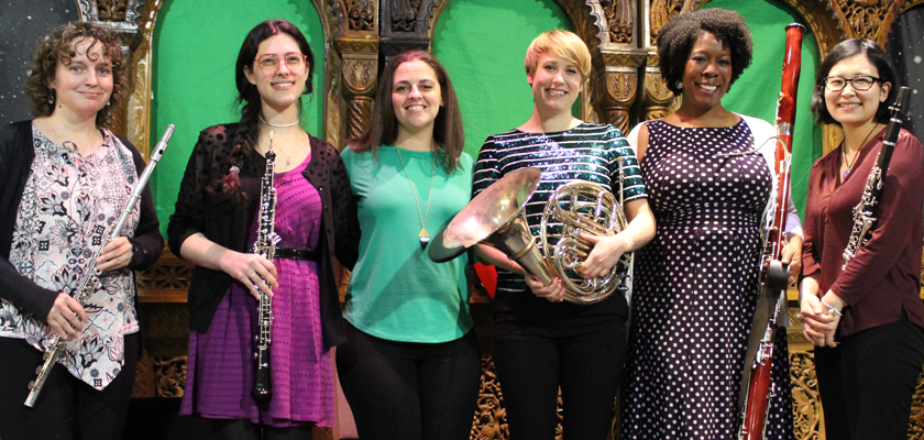 Image: Six women stand, smiling into the camera and holding woodwind and brass instruments against a colorful green backdrop.