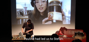 Image: A screengrab from a streaming performance-in-process. One woman is on a stage standing at a table opening a glass container. Another woman is pictured on a screen behind her, holding a glass jar filled with juice. We assume the jar they both are holding is the same.