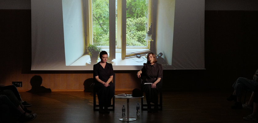 Image: Two women are seated on a stage. One is speaking, the other is silent. Behind them is a screen displaying a still photo of an open widown.