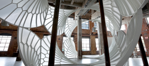 A light, airy, cathedral-like structure installed in a tall industrial space.