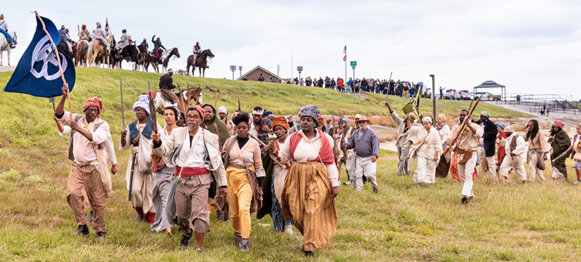 """Image Detail: Dread Scott's """"Slave Rebellion Reenactment,"""" featuring contemporary people in historical garb, marching in Louisiana and armed with prop machetes, sickles, and muskets with flags flying."""