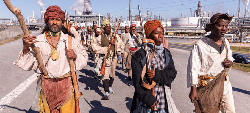 """Image Detail: Dread Scott's """"Slave Rebellion Reenactment,"""" featuring contemporary people in historical garb, marching in Louisiana and armed with prop machetes, sickles, and muskets."""