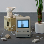 Image: An exhibition view shows a group of objects assembled on the concrete floor. Two 1980's era Macintosh computers are surrounded by a plaster cast polyhedron, stones, wires, cast resin Apple mice, a partial 3D print of the bust of Nefertiti, and a plastic plant. The computer screens display black and white images of other plastic plants that can be purchased on the internet.