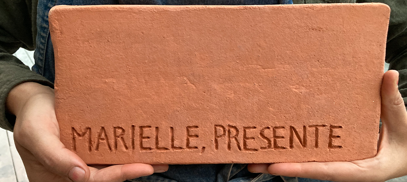 """Two hands holding a brick that says """"Marielle, presente"""""""