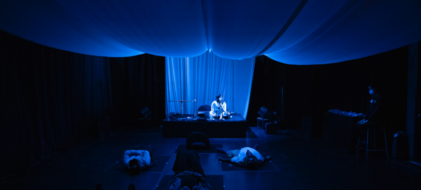 Image: Fabric is draped from the ceiling and the whole room is bathed in deep blue lighting. A Black woman sits on a stage with a microphone in her hand, surrounded by tank drums, electronics and a laptop. In front of her are four people lying down on rounded cushions on a black floor, spaced out six feet apart. By the entrance of the of the room, an attendant sits on a stool.