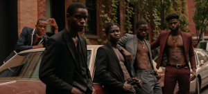 Image: Detail of a photograph of five individuals wearing blazers (some shirtless underneath) and dress pants, leaning against a maroon-colored vintage car; the image features earthy moody tones and various shades of Black skin.