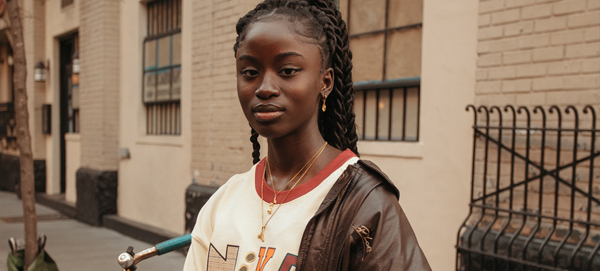 Image: Beautiful dark-skinned woman photographed in an urban environment with gold color tones bouncing throughout the image.