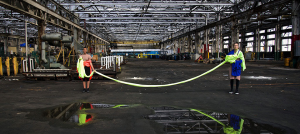 Two women stand in an abandoned industrial warehouse, connected by a chord of fabric. Their image is reflected in a puddle in front of them.