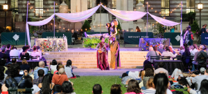 """Image: View from the audience of a performance at Bryant Park; actors appear in a non-traditional stage setting as part of """"Bryant Park Shakespeare"""" as the crowd enjoys from the grass and chairs."""