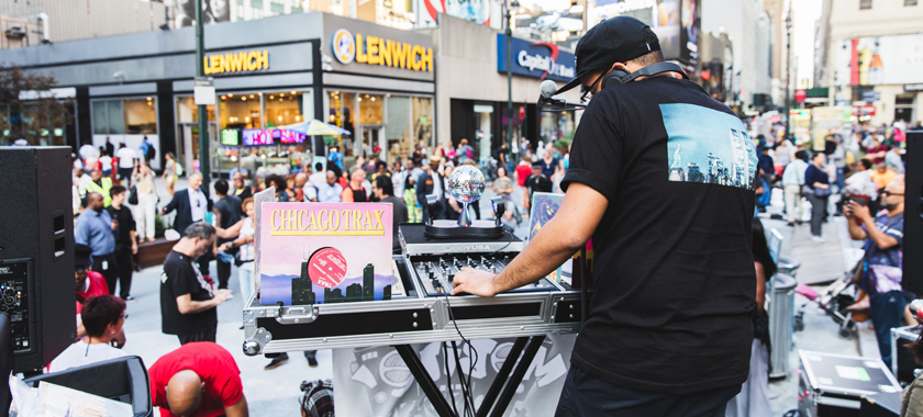"""Image: A DJ wearing a black tee shirt, pants, and a hat performs at Plaza33 with turntables and electronic equipment; a record called """"CHICAGOTRAX"""" is propped up with their setup."""