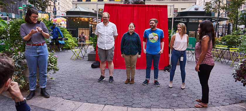 Image: Small outdoor improv comedy performance; four individuals stand together in a row, with two other individuals at the outskirts.