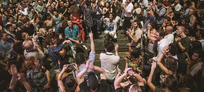 Image: A close-up photo of a crowd gathering at Bryant Park; audience members clap and dance and several individuals towards the center of the crowd hold instruments.
