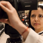 Photo of Luz Zamora looking into the small screen of a camera while adjusting the focus lens.