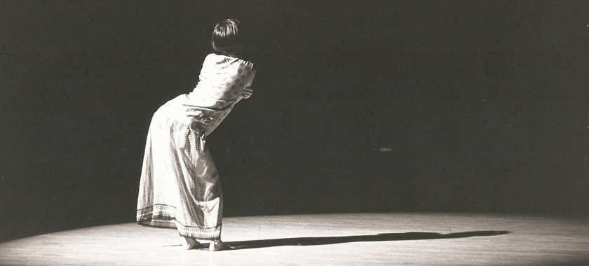 Image: Black and white photo of a solo performer on a stage; they are under a bright spotlight, and are pictured from behind in a dramatic pose.