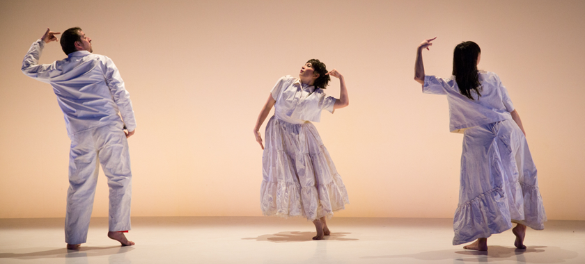 """Image: Photo by John Cyr for """"State of Heads."""" Three performers in white against a white backdrop and floor, evenly spaced apart. Left figure, Levi Gonzales is facing back, leaning to the left with left finger pointing to head, center figure, Rebecca Serrell Cyr, is facing front, leaning to the leaning to the left with left finger pointing to head, figure on the right, Hristoula Harakas is facing back, leaning to the left with left finger pointing to head."""