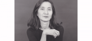 Image: Black and white portrait of choreographer Donna Uchizono. She has slightly below shoulder length dark hair and wears a crew-neck black tee-shirt and silver hoop earrings.