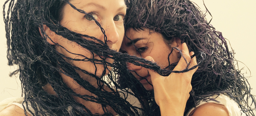 Image: Two performers photographed close up, one with face turned but eyes directly at the viewer, hand cradling the face of another performer who is less visible. Both wear wigs that appear to be made of straw.