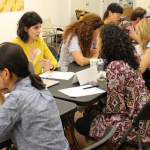 Image Detail: Long, rectangular tables are lined up in a large, wood-floored and white-walled gallery space. Individuals are paired across from each other, speaking animatedly with one another during an Immigrant Artist Mentoring Program event in 2017.