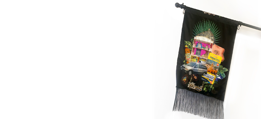 Image: photo of a black flag with fringe and elaborate embroidery featuring a mini van, Pine Sol, an international calling card, a doll's house, and other cultural references from the artist's childhood.