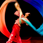 Image: a dancer is photographed against a black background, pictured in motion with a rainbow-colored long silk ribbon.