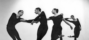 Image: Detail of a black and white photograph by Robert Rauschenberg featuring five dancers from Merce Cunningham's company in various stages of movement wearing all black.