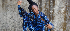 Image: Detail of a photograph of Nigerian-British musician Wunmi, pictured wearing a black leotard with blue and white water pattern and extra-long fringe on the arms that Wunmi pulls taut across the frame.